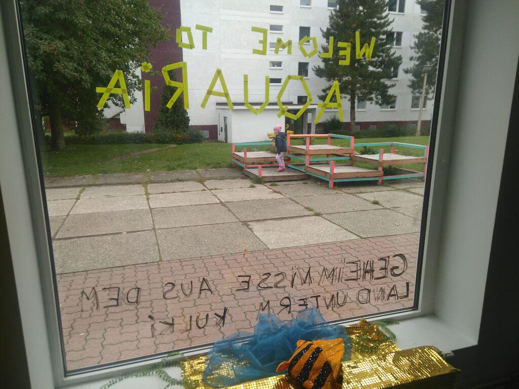 Welcome to Aquaria, Schriftzug mit Klebeband auf Schaufenster, Stoff-Fisch